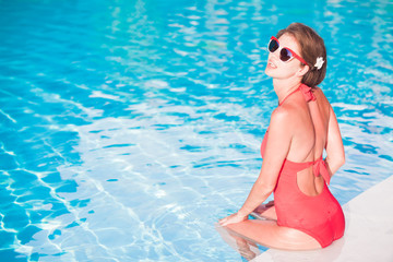 young longhaired woman in red bikini relaxing in luxury pool
