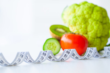 Diet. Fitness and healthy food diet concept. Balanced diet with vegetables. Fresh green vegetables, measuring tape on white background. Closeup