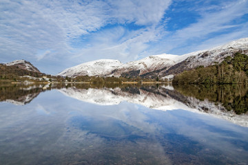 A perfect reflection of snow covered mountains and dramatic sky in the still waters of Grasmere, Lake District National Park, UNESCO World Heritage Site, Cumbria, England, United Kingdom, Europe