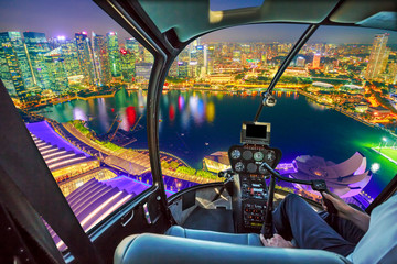 Helicopter cockpit interior flying on Singapore marina bay with financial district skyscrapers at night reflected on the harbor. Scenic flight above Singapore skyline. Night urban aerial scene.