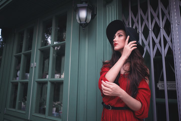 Elegant brunette young woman wearing red dress and straw hat on the street cafe. Fashion and style.