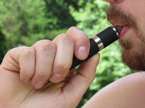Close up of an unrecognizable man using a vape pen or vaporizer