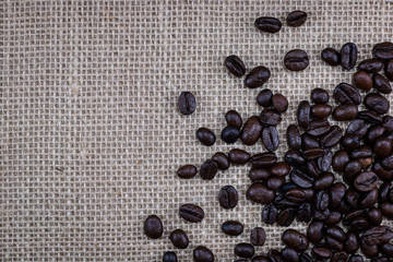 close up pattern coffee beans on sack background . black and brown color seeds with copy space .
