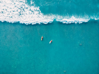 Aerial view of surfers and wave in tropical ocean. Top view