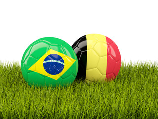 Brazil vs Belgium. Soccer concept. Footballs with flags on green grass