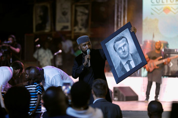 Nigerian singer Banky W holds a portrait of French President Emmanuel Macron, painted by a 11-year old Waris Kareem, during Macron's visit to the Afrika Shrine nightclub in Nigeria's commercial capital Lagos