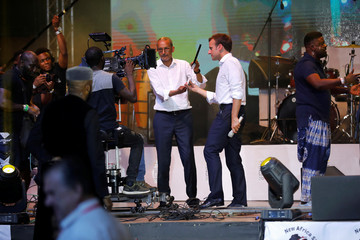 French President Emmanuel Macron holds a film slate and a microphone during a mock performance of a Nollywood film on stage during his visit to the Afrika Shrine nightclub in Nigeria's commercial capital Lagos