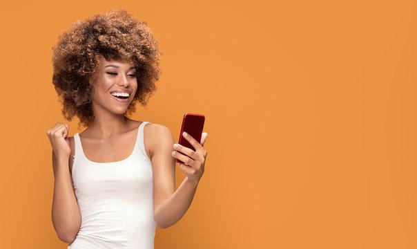 Cheerful afro woman using smart phone.