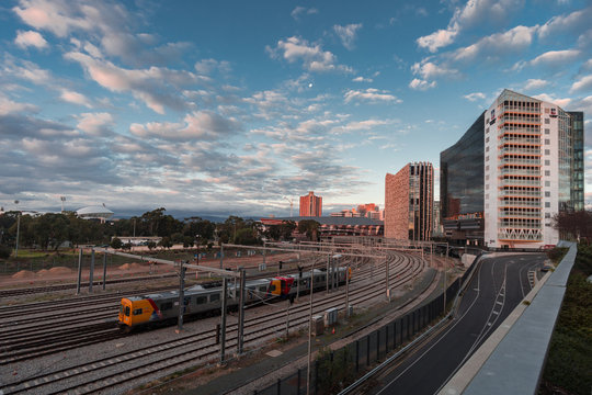 Train leaves the city of Adelaide as the sun sets