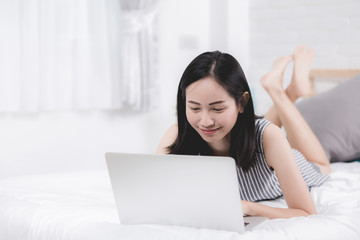 Woman rest and relaxing on bed using laptop computer