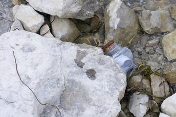 Message in bottle stuck under a rock