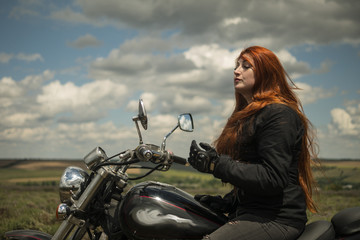 The red-haired biker girl is sitting on a motorcycle. field of meadow and clouds