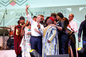 French President Emmanuel Macron takes a selfie with Nollywood actors on a stage during his visit to the Afrika Shrine nightclub in Nigeria's commercial capital Lagos