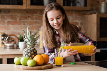 child health and development. useful and tasty drink. vitamin orange juice for balanced nutrition. little girl pouring fresh fruit beverage from a bottle