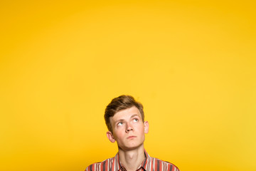 uncomprehending bewildered puzzled perplexed wondering man looking upwards. portrait of a young guy on yellow background pop up or peek out from the bottom. free space for advertising. Wall mural
