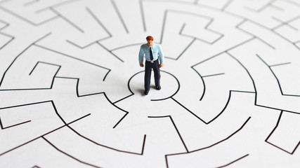 A miniature man standing in the middle of a maze.