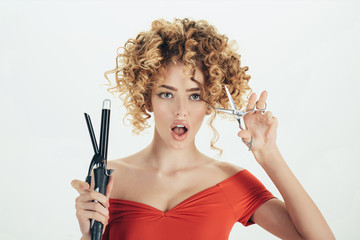 Hairdresser. Surprised curly hair girl holds hairdresser equipment. Beauty industry profession. Beauty and style. Makeup and cosmetics for hair care. Isolated on white background. Hairdresser tool.