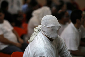 A person deported from the U.S. waits to be processed at an immigration facility in San Salvador