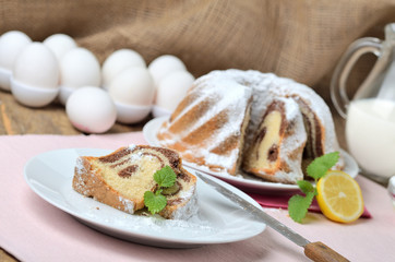Cut of marble cake sprinkled with sugar, lemon, melissa, milk, eggs and butter