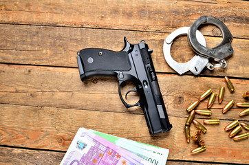 View from above of 9mm pistol - handgun, handcuffs, bullets, euro banknotes on old wooden table