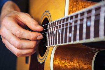 Closeup of guitarist practicing with acousic guitar.