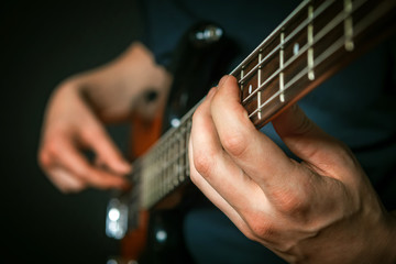 Rock guitarist practicing with bass guitar.