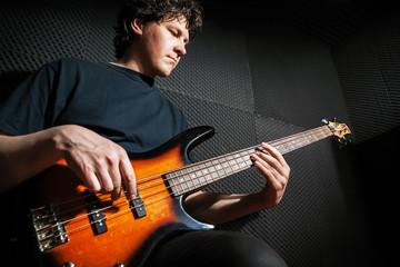 Handsome rock bass guitarist practicing.