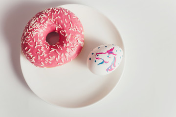 Easter eggs with donuts on the white table
