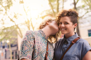 Smiling woman being kissed on the cheek by her girlfriend