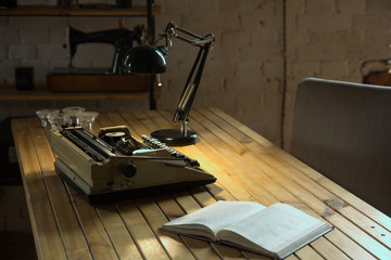 An old typewriter illuminated by a lamp on a wooden lacquered table