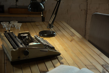 Typewriter illuminated by a table lamp on a wooden table