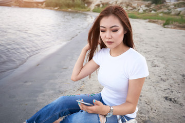 Cute asian girl holding modern mobile  phone and leads in social network or post photos, laughing and smiling,