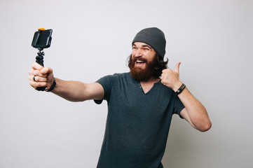Cheerful young bearded man showing thumb up and taking a selfie with his smartphone with selfie stick.