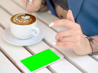 Mockup image of white mobile phone with green screen and hand holding phone. coffee on the table.