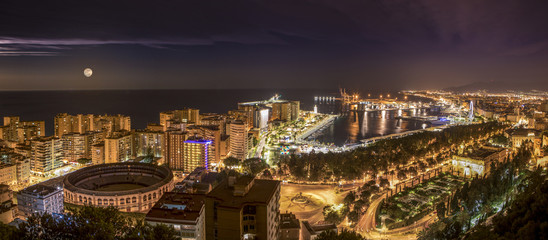 Night cityscape of Malaga city with the mediterranean sea and the port in the background.