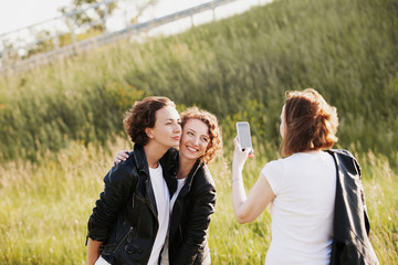 Pretty slim mom takes pictures on smartphone her adult positive beautiful daughters walking in the park in the same clothes and white T-shirts in jeans and leather jackets