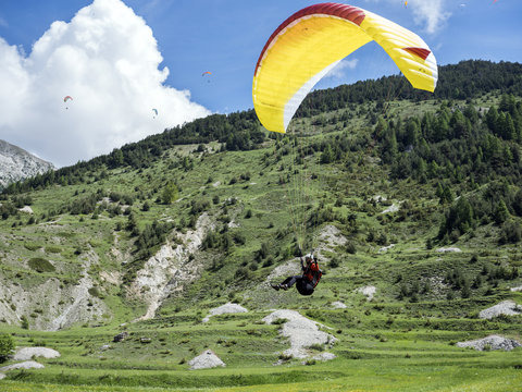 paraglider lands on grassy field between mountains in the frech haute provence near ceillac