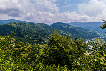 Magnificent landscape of mountainous terrain with valleys lying in her houses by the river