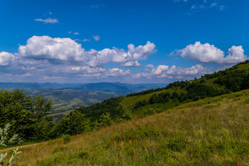 grassy sloping descent, overlooking the countryside of the mountains and hills under the blue sky