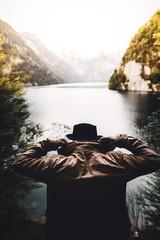 Mann mit Jacke und Hut schaut auf den Königsee beim Sonnenuntergang