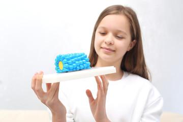 Jak dbać o zdrowie. Nastolatka ogląda model wirusa.