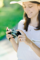 A girl with a camera in her hands, with a hat on her head