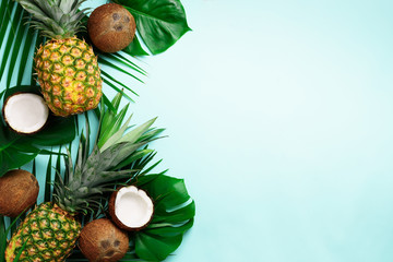 Foto auf AluDibond Palms Exotic pineapples, ripe coconuts, tropical palm and green monstera leaves on blue background with copyspace for your text. Creative layout. Summer concept. Flat lay, top view