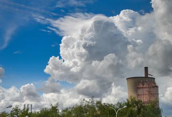 Ciel bleu avec un énorme nuage cumulonimbus au dessus d'une cheminée d'un centrale électrique