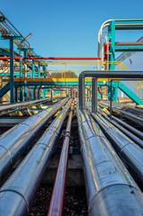 Perspective de tuyaux chromés sur fond de ciel bleu dans une usine pétrochimique