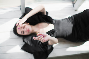 The young bewitching brunette woman in a black dress lying on the floor indoors
