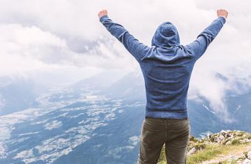 Mann in Siegespose am Berggipfel