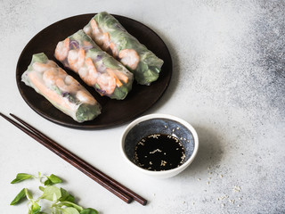 Three Vietnamese spring rolls - carrots, cucumber, corn salad, red cabbage, herbs and shrimps on a wood dark plate. Soy sauce with sesame seeds in bowl on a gray background