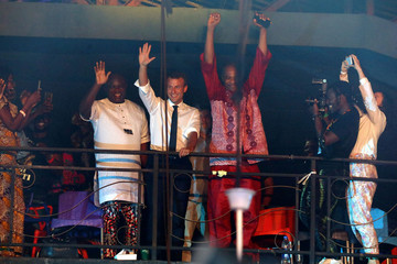 French President Emmanuel Macron and artist Femi Kuti wave to the crowd during a visit to the Afrika Shrine during a live show in Lagos