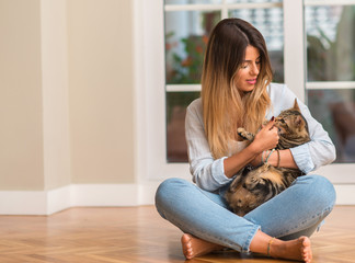 Young beautiful woman sitting on the floor smiling and playing with cat.